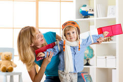 Child boy dressed like a pilot with toy wings playing at home Royalty Free Stock Photo