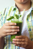Child boy drinking green smoothie Royalty Free Stock Images