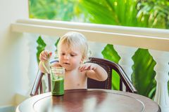 Child boy drinking healthy green vegetable smoothie - healthy eating, vegan, vegetarian, organic food and drink concept.  royalty free stock image