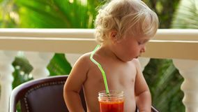 Child boy drinking and playing with a healthy vegetable-fruit smoothie - healthy eating, vegan, vegetarian, organic food. And drink concept stock video footage