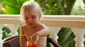 Child boy drinking and playing with a healthy vegetable-fruit smoothie - healthy eating, vegan, vegetarian, organic food. And drink concept stock footage