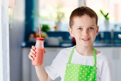 Child boy drinking strawberry smoothie. From glass with straw Stock Photo
