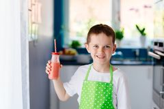 Child boy drinking strawberry smoothie. From glass with straw Royalty Free Stock Images