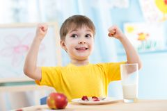 Child boy eating healthy food and showing his Stock Image