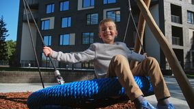 Child boy enjoy at swing at playground near home