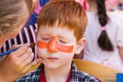 Child boy face painting, making tiger eyes process Royalty Free Stock Image