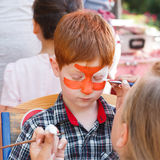 Child boy face painting, making tiger eyes process Royalty Free Stock Images
