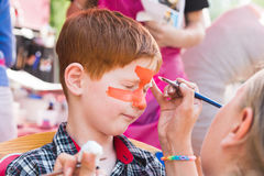 Child boy face painting, making tiger eyes process Stock Photo