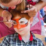 Child boy face painting, making tiger eyes process Stock Images