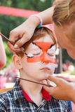 Child boy face painting, making tiger eyes process Royalty Free Stock Photo