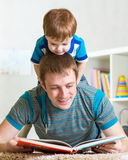 Child boy and father read a book on floor at home Royalty Free Stock Photography