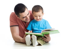 Child boy and father read a book on floor at home Stock Photos