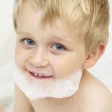 Child boy with a foam on the face in the bath Royalty Free Stock Images