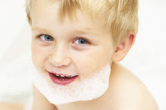 Child boy with a foam on the face in the bath Stock Image