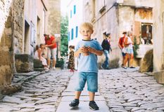 Child boy with Fritule - Croatian sweet pastry, cookies, homemade fritters. Cute kid boy with Fritule - homemade fritters with chocolate on city street of stock images