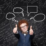 Child boy with ginger hair showing thumb up on blackboard background. Smart kid in glassed with science  formulas. And bubble clouds stock photography