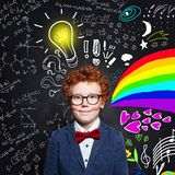 Child boy with ginger hair wearing glasses on blackboard background with science formulas, art pattern and light bulb idea concept.  royalty free stock photo