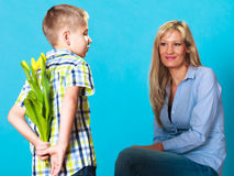 Child boy giving flowers his mother. Holiday mother's day concept. Rear view little boy with bunch of yellow tulips behind back preparing nice surprise for his Royalty Free Stock Images