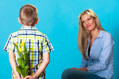 Child boy giving flowers his mother. Holiday mother's day concept. Rear view little boy with bunch of yellow tulips behind back preparing nice surprise for his Royalty Free Stock Photo