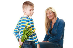Child boy giving flowers his mother. Holiday mother's day concept. Rear view little boy with bunch of yellow tulips behind back preparing nice surprise for his Stock Image
