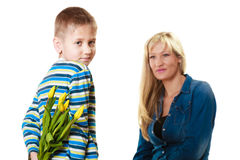 Child boy giving flowers his mother. Holiday mother's day concept. Rear view little boy with bunch of yellow tulips behind back preparing nice surprise for his Stock Photography
