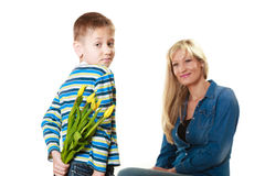 Child boy giving flowers his mother. Holiday mother's day concept. Rear view little boy with bunch of yellow tulips behind back preparing nice surprise for his Stock Photos