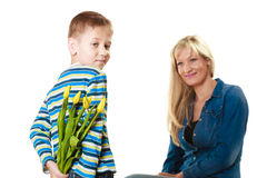 Child boy giving flowers his mother. Holiday mother's day concept. Rear view little boy with bunch of yellow tulips behind back preparing nice surprise for his Stock Images