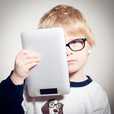 Child boy in glasses holding tablet pc Stock Photography