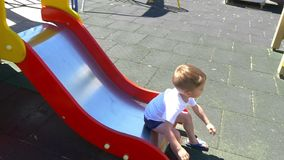A child boy with a great pleasure rides a slide on a playground in a slow motion. Slow motion stock footage