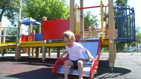 Child boy with great pleasure, rolling on a slide on the playground. Slow motion stock video footage