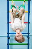 Child boy hanging on gymnastic rings Royalty Free Stock Photos