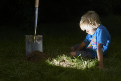 Child boy have unearthed a treasure in the grass Royalty Free Stock Photography