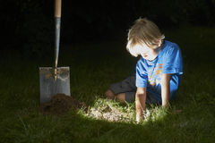 Child boy have unearthed a treasure in the grass Stock Photography