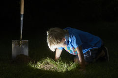 Child boy have unearthed a treasure in the grass Royalty Free Stock Photo