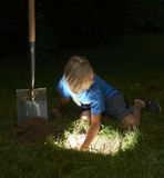 Child boy have unearthed a treasure in the grass Royalty Free Stock Photos