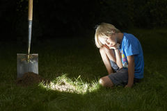 Child boy have unearthed a treasure in the grass Stock Image