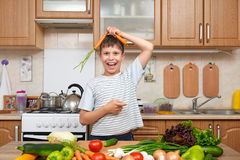 Child boy having fun with carrot. Home kitchen interior with fruits and vegetables. Healthy food concept Royalty Free Stock Images