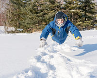 Child Boy Having Fun in the Snow. Child boy doing the dolphin jump in the fresh snow of the Canadian Winter, having fun with the simple free things Stock Photography