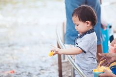 Child boy having fun to feed and give food to fish Royalty Free Stock Photo