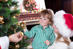 Child boy helps mother and father to decorate. Child boy helps his mother and father to decorate family Christmas tree Royalty Free Stock Image