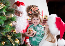Child boy helps mother and father to decorate. Child boy helps his mom and dad weared Santa Claus to decorate family Christmas tree Royalty Free Stock Photography
