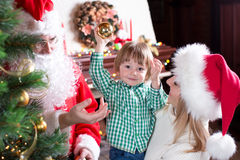 Child boy helps mother and father to decorate. Child boy helps his mother and father weared Santa Claus to decorate family Christmas tree Royalty Free Stock Photography