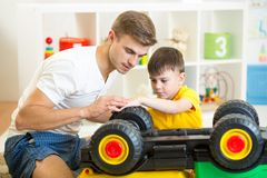Child boy and his father repair toy car Royalty Free Stock Photos