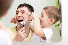 Child boy and his father shave looking at mirror Royalty Free Stock Photo