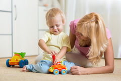 Child boy and his mother repair toy car at home Stock Photography