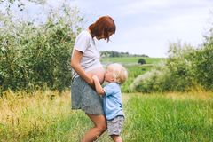 Child boy kissing belly of pregnant her mother on nature backgro. Child boy hugging and kissing belly of pregnant her mother against green nature background royalty free stock photography