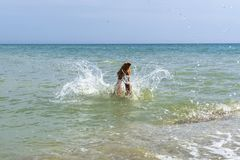 The child boy is jumping into the sea.  stock photo