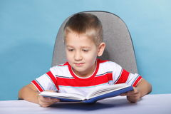 Child boy kid reading a book on blue. Young boy reading a book, child kid on blue background holding an open book Royalty Free Stock Photos