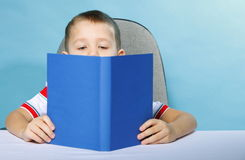 Child boy kid reading a book on blue. Young boy reading a book, child kid on blue background holding an open book Royalty Free Stock Photography