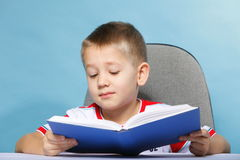 Child boy kid reading a book on blue. Young boy reading a book, child kid on blue background holding an open book Stock Photography